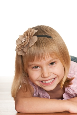 A laughing lying little girl is looking forward; isolated on the white background Stock Photo - 11266579