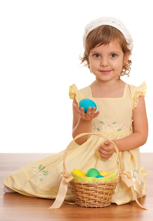 A little girl sitting on the floor near the Easter basket and holding an egg photo