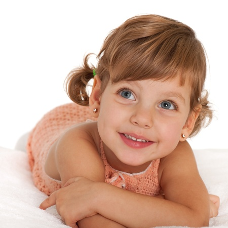 bedspread: A happy little girl is lying on the bedspread; isolated on the white background
