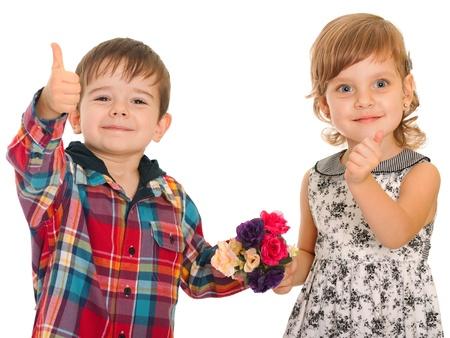 niño y niña: Una chica alegre y un muchacho sonriente está sosteniendo sus pulgares hacia arriba, aislado en el fondo blanco