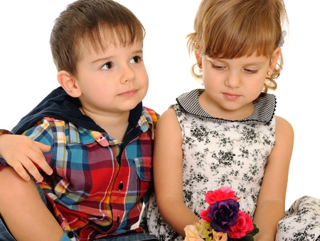 A serious girl and a boy are holding flowers; isolated on the white background photo