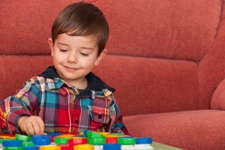 bambini pensierosi: Un bambino sta giocando al tavolo