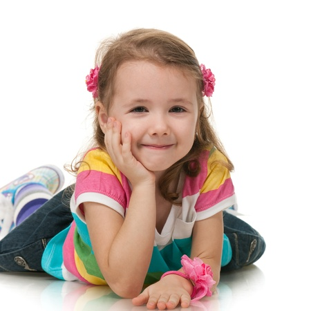 A smiling little girl is lying; isolated on the white background photo