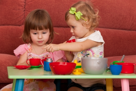 Two little girls are playing at the table