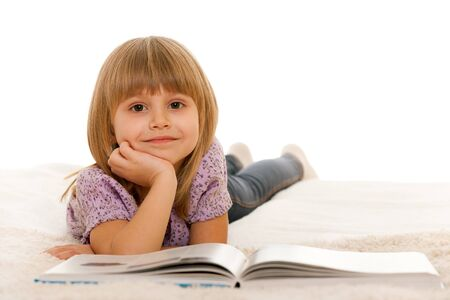 pleasure of reading: A little girl is reading a book on the carpet; isolated on the white background