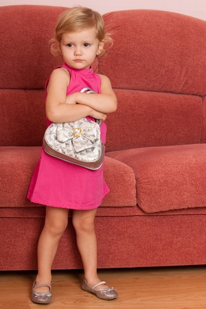 A serious little girl is standing in front of the sofa