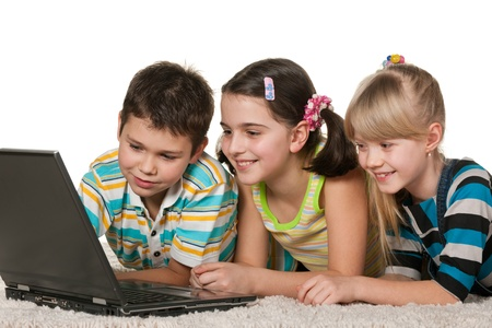 Three cheerful children with a laptop are lying on the carpet; isolated on the white background