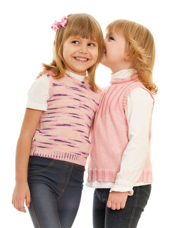 preschool kids: One little girl whispers something her friend; isolated on the white background