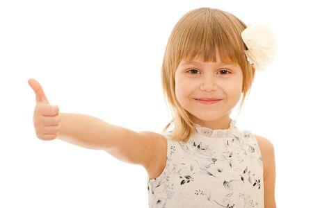 A smiling little girl holding her thumb up; isolated on the white background Stock Photo - 12390357
