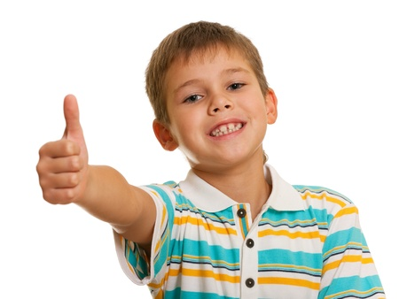 A portrait of a smiling boy holding his thumb up; isolated on the white background photo