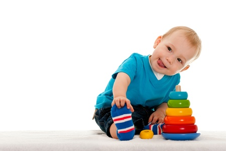 A little boy is playing with toys on the blanket; isolated on the white background photo