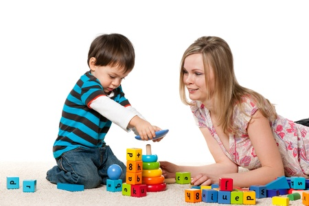 Young mother and a little son are playing on the carpet with blocks