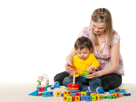 Mother and son playing on the carpet with toys; isolated on the white background