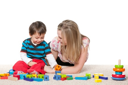 babysitter: Mother and a little son are playing on the carpet with blocks; isolated on the white background Stock Photo