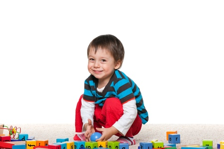 boys only: Little cheerful boy is playing with blocks on the carpet
