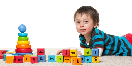 A little boy is playing with blocks on the carpet; isolated on the white background photo