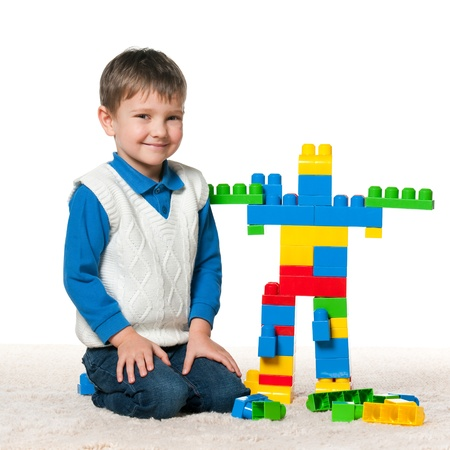boys toys: Little boy is playing with meccano on the carpet Stock Photo