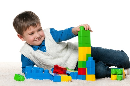 A little smiling boy is playing with blocks on the carpet; isolated on the white background