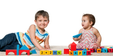 A smiling boy and a baby girl are playing with blocks on the carpet; isolated on the white background photo