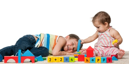 A laughing boy and a baby girl are playing with blocks on the carpet; isolated on the white background