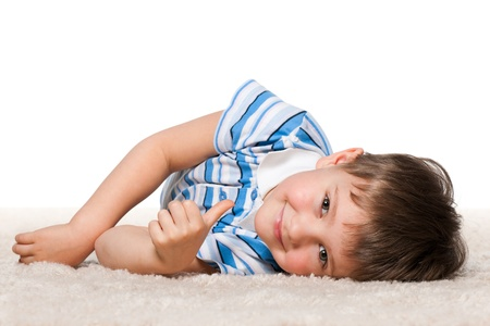 lying on side: A cheerful little boy is lying on the white carpet; isolated on the white background