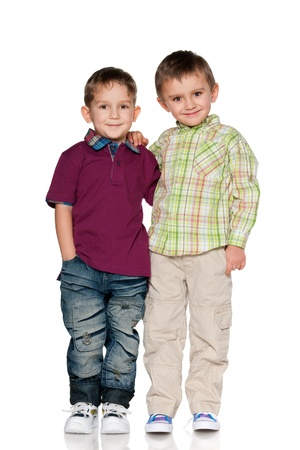 american children: Two boys are standing together; isolated on the white background
