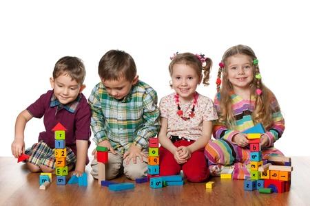 juguetes de madera: Cuatro ni�os est�n jugando en el suelo juntos, aislados sobre el fondo blanco
