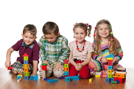 preschool children: Four children are playing on the floor together; isolated on the white background