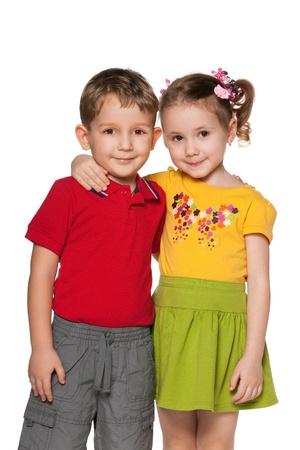 Een jongen en een meisje met elkaar staan, geïsoleerd op de witte achtergrond Stockfoto