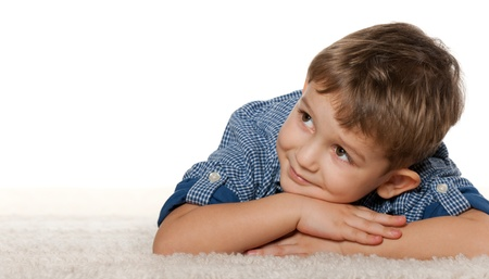 A thoughtful boy is dreaming on the carpet; isolated on the white background Stock Photo