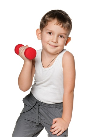 The boy is doing morning exercises with dumbbells; isolated on the white background photo