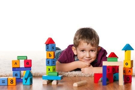 A little boy is lying on the floor near toys