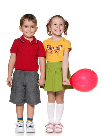 ni�o parado: Ni�o feliz y una ni�a con el globo est�n de pie juntos, aislados sobre el fondo blanco
