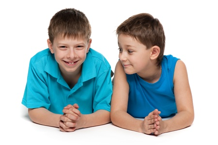 Two handsome little boys are lying together; isolated on the white background Stockfoto