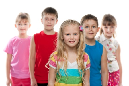 A little girl stands in front of a group of children, focus is on the girl; isolated on the white background photo