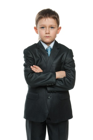 A portrait of a confident little boy in black suit; isolated on the white background photo