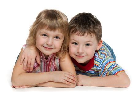 niño y niña: Un niño y una niña están acostados juntos, aislados sobre el fondo blanco