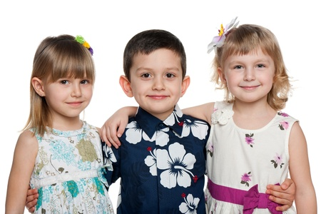 Three children are standing together; isolated on the white background photo