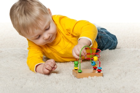 A little boy is playing with toy on the carpet Stock Photo - 13024746