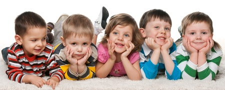 preschoolers: A little girl is lying at four little boys on the carpet
