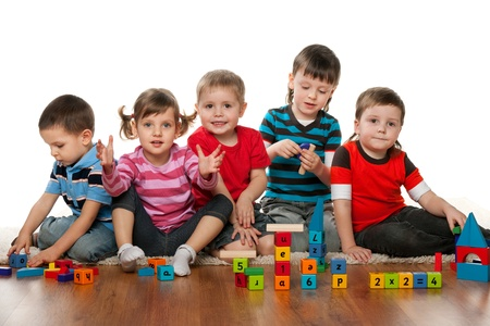 kinder: Cinco ni�os est�n jugando juntos en la cancha Foto de archivo
