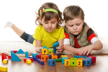 juguetes de madera: Dos ni�os est�n jugando en el suelo juntos, aislados sobre el fondo blanco