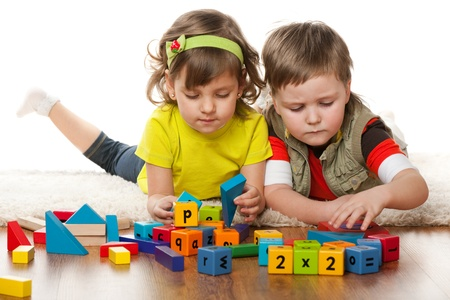 Dos niños están jugando en el suelo juntos, aislados sobre el fondo blanco Foto de archivo - 13024763