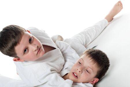 kinderen: Twee jongens worstelen, op de witte achtergrond