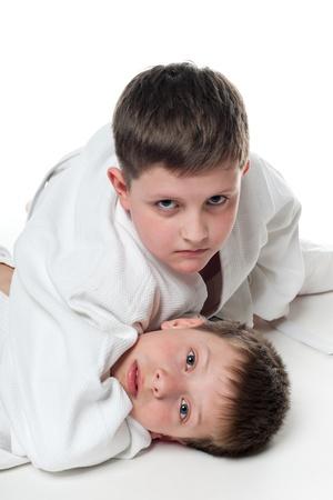 judo: Lucha de dos niños, en el fondo blanco