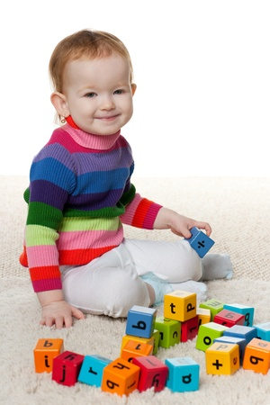 play blocks: Little cheerful redhead girl is playing with blocks on the carpet