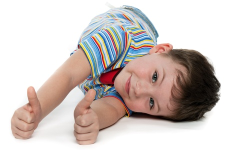A lying little boy is holding his thumbs up; on the white background Stock Photo - 14357911