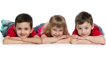 A portrait of a group of three cheerful children; on the white background