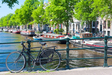 A bicycle stands on the bridge through the channel in Amsterdam photo