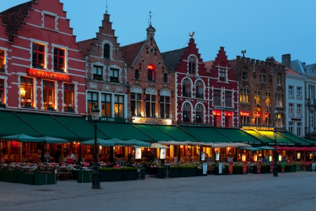 Bruges, Belgium - May 21, 2012: Old buildings and small cafes located on the Grote Markt, one of the main sightseeing places of Bruges in the evening of May 21, 2012. GPS information is in the file